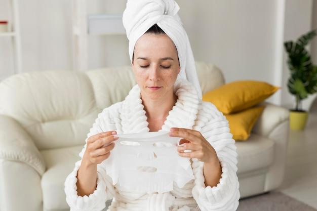 Vrouw die haar gezichtsmasker kijkt