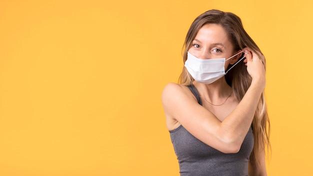 Vrouw die haar gezichtsmasker met exemplaarruimte opstijgt