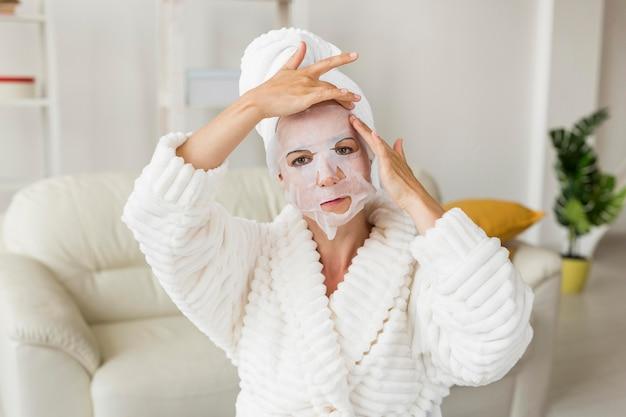 Vrouw die haar gezichtsmasker middelgroot schot toepast