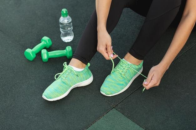 Vrouw die haar groene tennisschoenen bindt