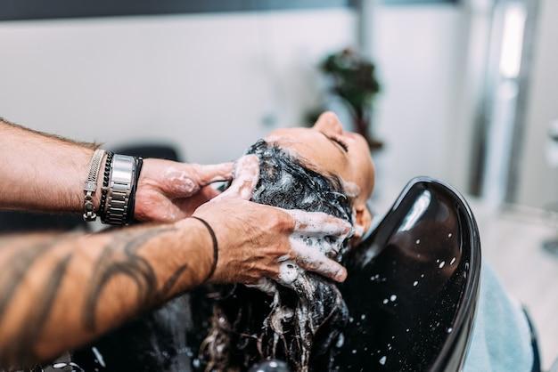 Vrouw die haar haar heeft dat bij een professionele haarsalon wordt gewassen.