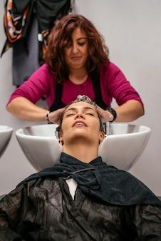 Vrouw die haar haar heeft dat in een salon wordt gewassen
