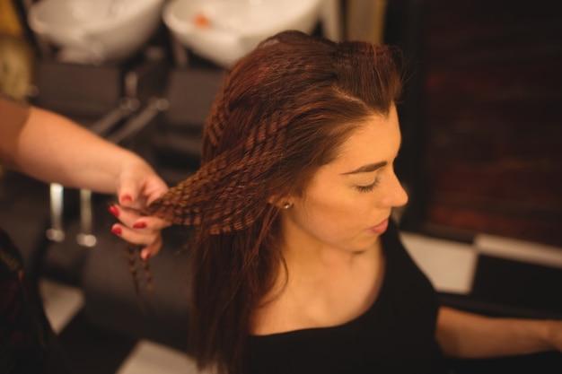 Vrouw die haar haar stileert bij salon