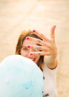 Vrouw die haar hand met blauwe suikerszijde toont