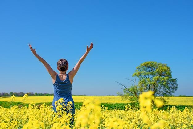 Vrouw die haar handen hoog opheft tegen bluhemel en gele koolzaadgebieden