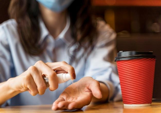 Vrouw die haar handen in een restaurant desinfecteert