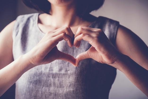 Vrouw die haar handen in hartvorm, hart ziekteverzekering