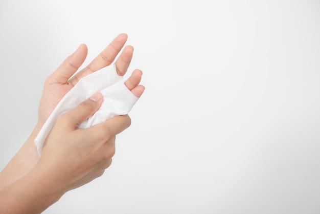 Vrouw die haar handen met een weefsel op witte achtergrond schoonmaakt