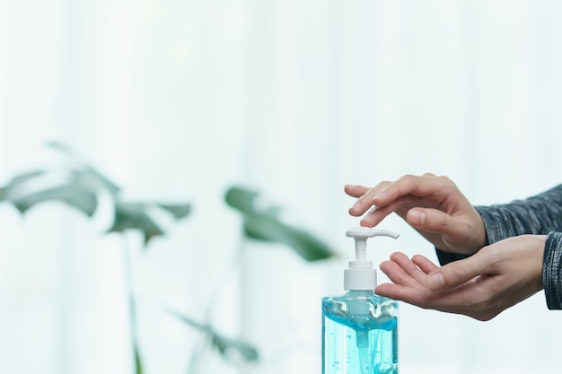 Vrouw die haar handen met ontsmettingsmiddel vloeibaar antibacterieel gel schoonmaakt, in quarantaine, het concept van het coronavirus.