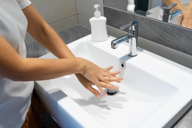 Vrouw die haar handen met zeep wast