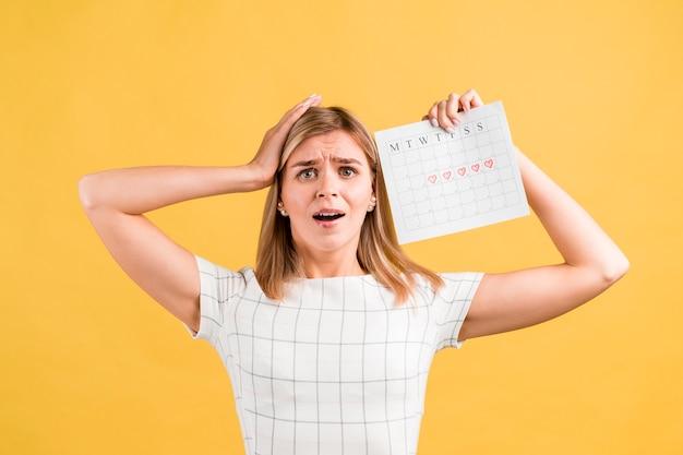 Vrouw die haar handen op haar hoofd en periodekalender zet
