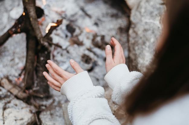 Vrouw die haar handen opwarmt