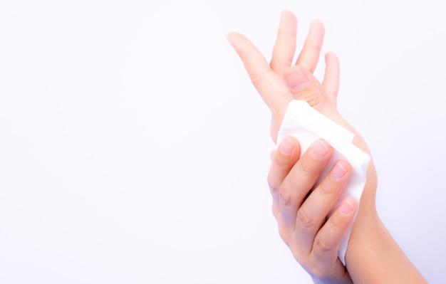 Vrouw die haar handen schoonmaakt door wit papieren zakdoekje te gebruiken.