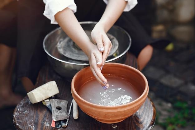 Vrouw die haar handen wast bij de aardewerkopslag