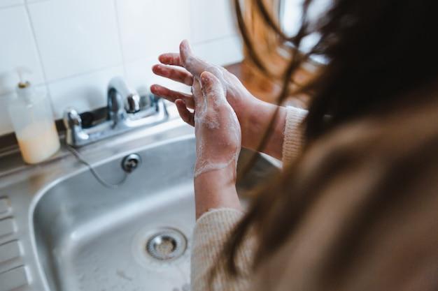 Vrouw die haar handen wast met zeep - het concept van coronavirus