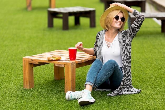 Vrouw die haar hoed in het park houdt