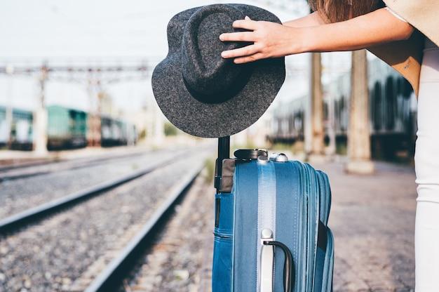 Vrouw die haar hoed op haar koffer op het treinstation plaatst.