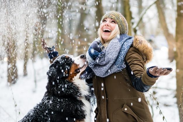 Vrouw die haar hond in de winter loopt en allebei de sneeuw onderzoekt