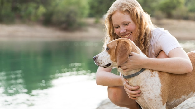 Vrouw die haar hond naast het meer aait