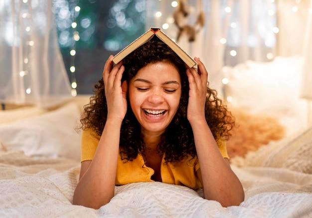 Vrouw die haar hoofd bedekt met boek vooraanzicht