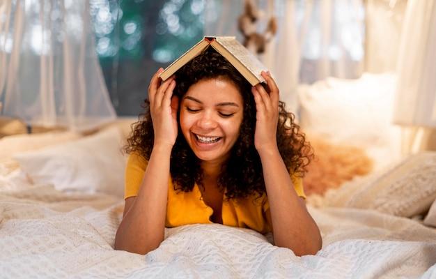 Vrouw die haar hoofd behandelt met boek