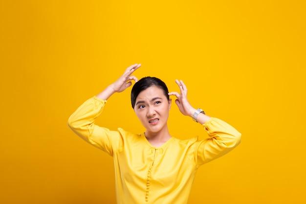 Vrouw die haar hoofd krast dat over gele muur wordt geïsoleerd