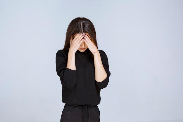 Vrouw die haar hoofd vasthoudt omdat ze moe is of hoofdpijn heeft.