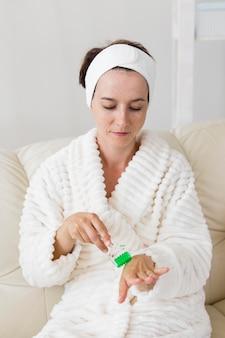 Vrouw die haar hoofdband gebruikt en haar handen masseert