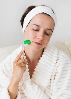 Vrouw die haar hoofdband gebruikt en het gezicht masseert