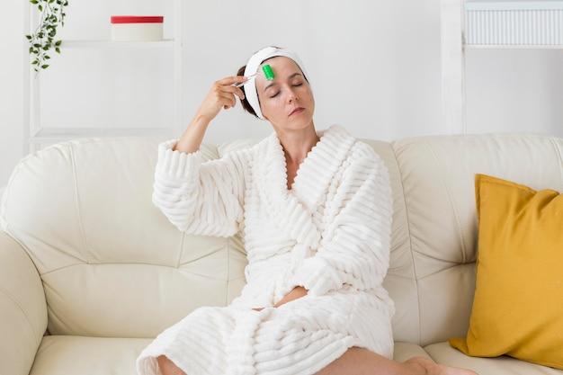 Vrouw die haar hoofdband gebruikt en het gezicht van de afstand masseert