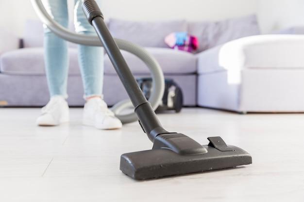 Vrouw die haar huis met stofzuiger schoonmaakt