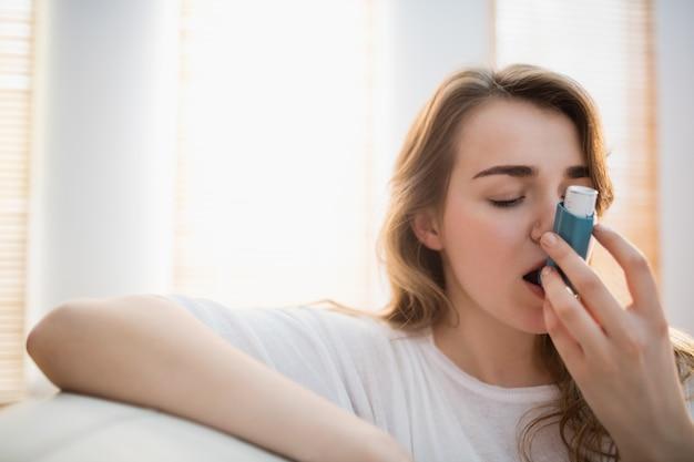 Vrouw die haar inhaleertoestel op laag in de woonkamer met behulp van