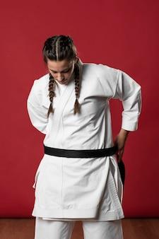 Vrouw die haar karatekimono bevestigt en neer kijkt