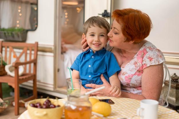Vrouw die haar kleinzoon op de wang wil kussen