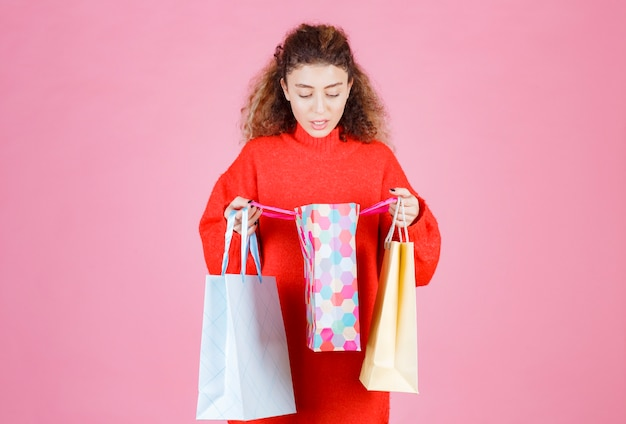 Vrouw die haar kleurrijke boodschappentassen opent en de producten controleert.