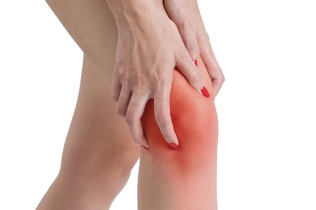 Vrouw die haar knie met rood hoogtepunt op pijngebied houdt dat op witte achtergrond wordt geïsoleerd.