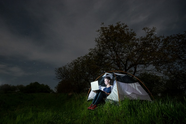 Vrouw die haar laptop in het kamperen bij nacht met behulp van. vrouw zitten in de tent onder bomen en nachtelijke hemel