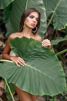 Vrouw die haar lichaam bedekt met een groot groen blad