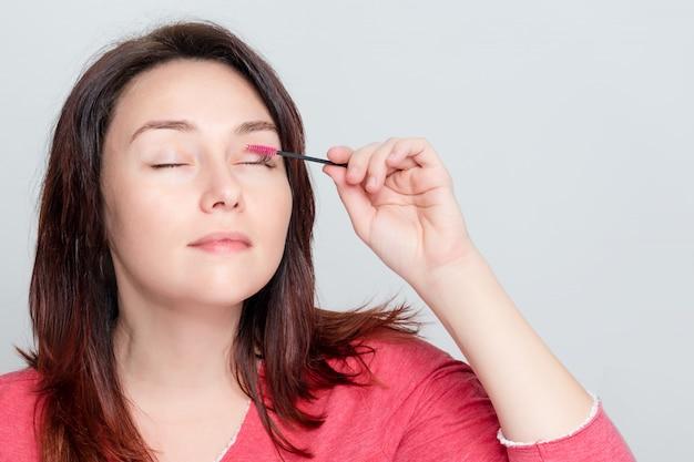 Vrouw die haar make-up doet, wimpers voorbereidt, wimpers borstelt met behulp van een penseel. cosmetische procedure voor wimperverzorging in het stadium van kammen. wimpers bouwen, schilderen, lamineren. copyspace voor tekst