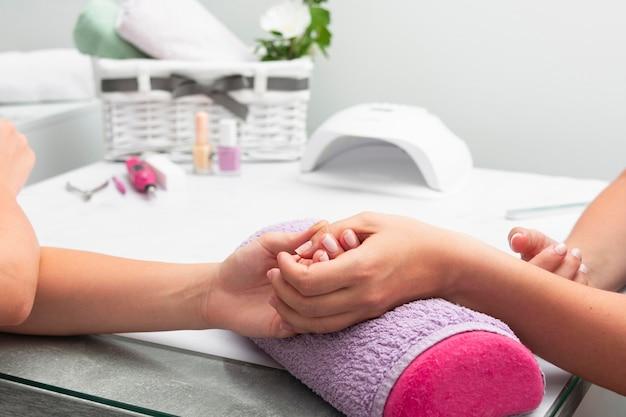Vrouw die haar manicure heeft die bij de salon met exemplaarruimte wordt gedaan