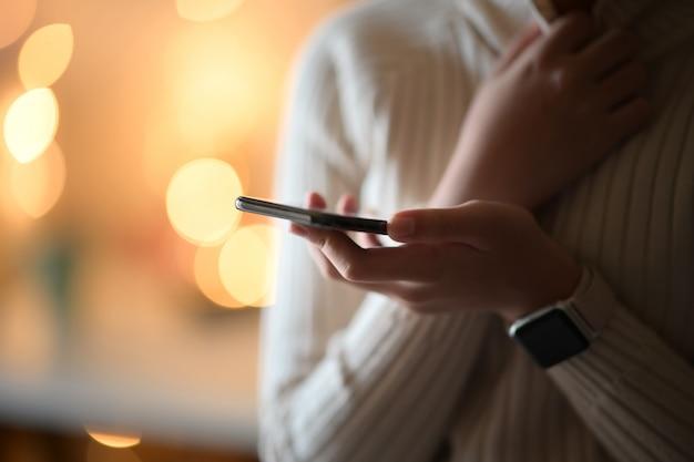 Vrouw die haar mobiele smartphone in de straatnacht met behulp van