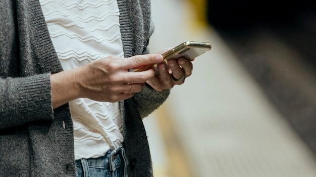 Vrouw die haar mobiele telefoon gebruikt tijdens het wachten op de trein tijdens de coronaviruspandemie