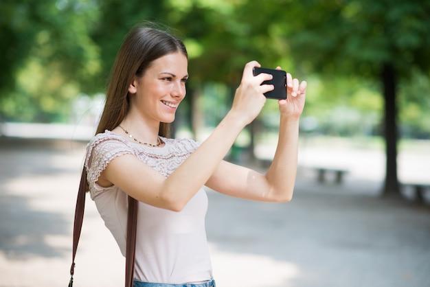 Vrouw die haar mobiele telefoon met behulp van om een foto te nemen
