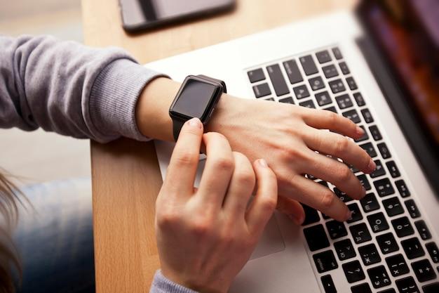 Vrouw die haar moderne smartwatch bekijkt