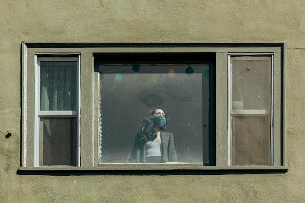 Vrouw die haar mond bedekt met een bandana die uit het raam staart tijdens de coronavirusvergrendeling.