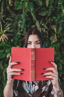 Vrouw die haar mond behandelt met boek die zich tegen groeiende installatie bevinden