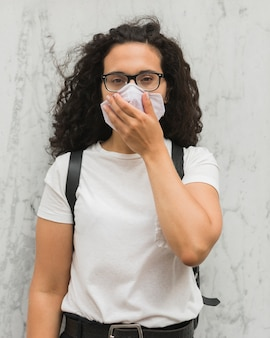 Vrouw die haar mond behandelt terwijl het dragen van medisch masker