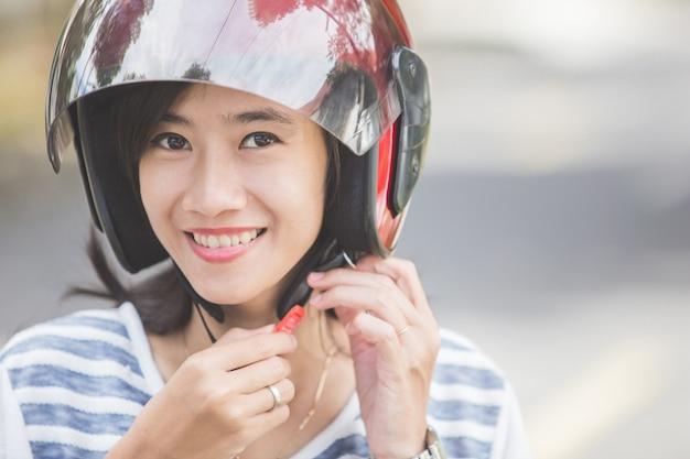Vrouw die haar motorhelm vastmaakt