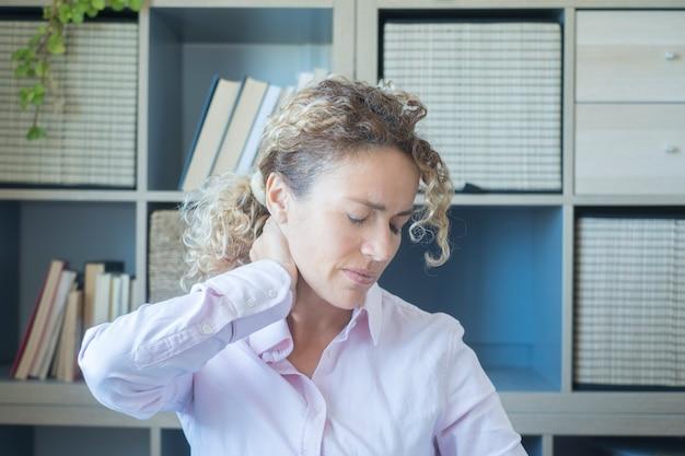 Vrouw die haar nek op kantoor aanraakt met hoofdpijn en pijn - stress en vermoeide mensen in slim werken - modern levensstijlconcept vrouwelijke volwassen jonge raak zijn hoofd aan met pijn