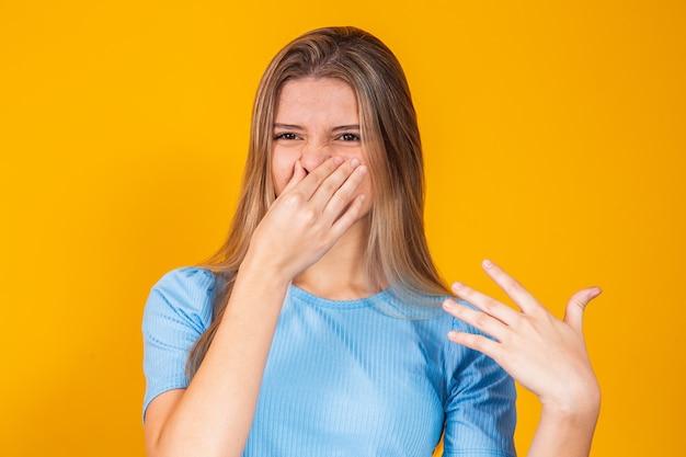 Vrouw die haar neus bedekt voor slechte geur, concept van stinkding, slechte adem, onaangename geur, rot voedsel, geur, lichaamsgeur; jong volwassene
